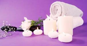 Ciottoli, candela, asciugamano e fiori stock footage