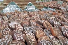 Ciottoli dal lago sacro Manasarovar con i geroglifici e il ` buddista principale del OM Mani Padme Hum del ` di mantra immagini stock