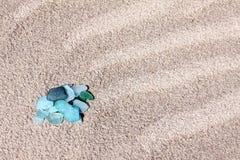 Ciottoli di vetro sulla sabbia Immagini Stock