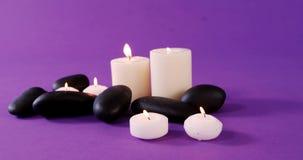 Ciottoli e candela sulla tavola video d archivio