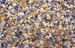 Ciottoli rotondi multicolori sulla spiaggia Bello fondo immagini stock