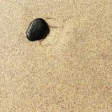 Ciottolo nero solo sulla sabbia Fotografia Stock