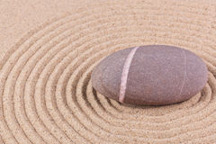 Ciottolo in un cerchio rastrellato della sabbia Immagine Stock Libera da Diritti
