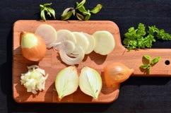 Cipolla e fette tagliate di cipolla sul tagliere Immagini Stock Libere da Diritti