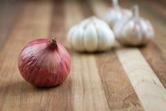 Cipolla ed aglio artistici sulla tavola di legno Fotografia Stock Libera da Diritti