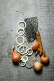 Cipolla fresca tagliata e vecchio scure su un supporto di pietra Immagini Stock Libere da Diritti