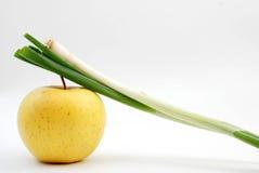 Cipolla organica della primavera sulla mela dorata Immagini Stock Libere da Diritti