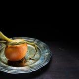 Cipolla organica, servita su un vassoio d'argento contro un legno scuro Fotografia Stock