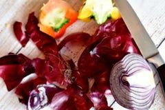 Cipolla porpora su un tagliere con cascame vegetale e bucce fotografie stock libere da diritti