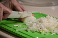 Cipolle di taglio con un coltello ceramico su un tagliere verde Immagine Stock Libera da Diritti