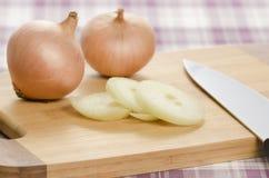 Cipolle e fette della cipolla sul tagliere. Fotografia Stock