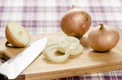 Cipolle e onionrings sul cuttingboard con il coltello. Fotografia Stock Libera da Diritti