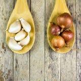 Cipolle ed agli sulla siviera di legno Fotografia Stock