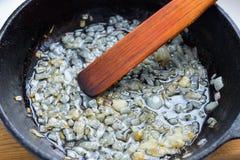 Cipolle fritte in una padella Fotografia Stock