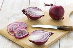 Cipolle rosse affettate su un tagliere con un coltello fotografia stock