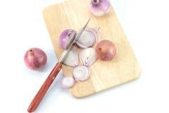 Cipolle rosse girate su un tagliere di legno da un'altezza immagini stock libere da diritti