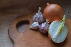 Cipolle, tre teste di aglio su un bordo di legno della cucina immagini stock libere da diritti
