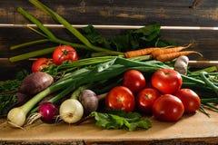 Cipolle verdi, aglio, carote, barbabietola e pomodori contro lo sfondo dei bordi grigi anziani Immagini Stock