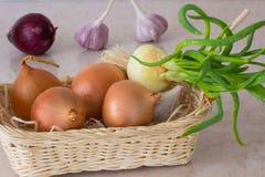 Cipolle verdi, aglio e cipolle rosse in canestro di vimini Immagini Stock