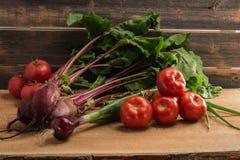 Cipolle verdi, barbabietola e pomodori contro lo sfondo dei bordi grigi anziani Immagine Stock