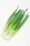 Cipolle verdi su priorità bassa bianca Immagine Stock