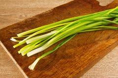 Cipolle verdi su un bordo di legno Fotografia Stock
