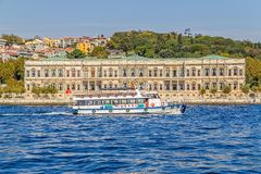 Ciragan Palace Kempinski Hotel. ISTANBUL, TURKEY - SEPTEMBER 29, 2013: Tourist boat floats in front of the Ciragan palace a former Ottoman palace is now a five Royalty Free Stock Photo