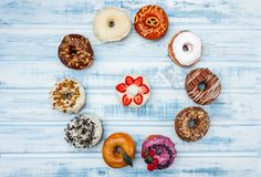 A circle of assorted donuts, on old wood background. Top view. stock photography
