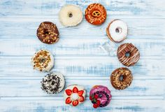 A circle of assorted donuts, on old wood background. Top view. Space for text stock photography