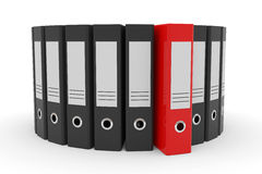 Circle of black office folders and one red. Stock Photos