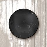 Circle blackboard at white wooden backdrop Stock Image
