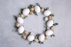 Circle border for easter card or invitation. Easter wreath with easter quail, chicken eggs and leaf sprigs of eucalyptus. On a gra. Y concrete background with royalty free stock image