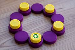 Circle of bottle caps with the logo of recycling royalty free stock photo
