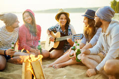 Circle of campers. Group of young campers with drinks and guitar spending evening by campfire Stock Image