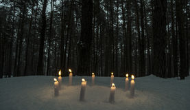 Circle of candles in dark winter forest Stock Photo
