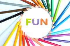 Circle colored pencils with alphabet sponge rubber of text. `FUN ` at center over white background stock illustration