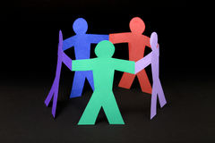 Circle of colorful paper people on black background Stock Photos