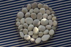 Circle composed of white and gray stones, pebbles mandala background on blue white striped background in daylight, life concept. Sunlight royalty free stock image