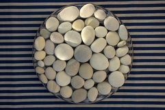 Circle composed of white and gray stones, pebbles mandala background on blue white striped background in daylight, life concept. Sunlight stock photography