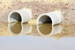 Circle concrete culvert. In earthen road with water Stock Images