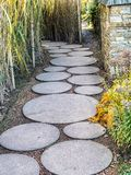 Circle concrete slab path. In the garden stock image