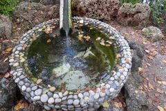 Circle decorative pond with pebble wall royalty free stock photography