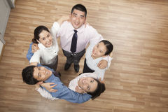 Circle of five smiling coworkers holding each other and looking up at camera, overhead shot Stock Photos