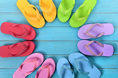 Circle of flip flops on blue painted beach decking, top view Stock Photos