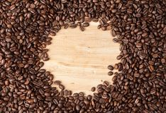 Circle frame of coffee beans on wooden table Stock Photography