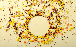 Circle frame made of sugar candies, pastry decoration on yellow background. Royalty Free Stock Photos