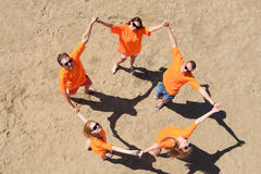 Circle of friends. Cheerful young people having fun on a beach. Great summer holidays Stock Images