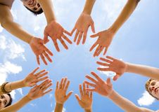 Circle of friends. Below angle of several teens keeping their hands in air in the form of circle Royalty Free Stock Photos