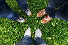 In a circle of friends. Group of friends standing in a circle on a spring meadow but only their feet in sneakers is visible Stock Photography