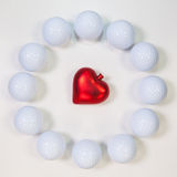 Circle of golf balls and red heart Stock Photos